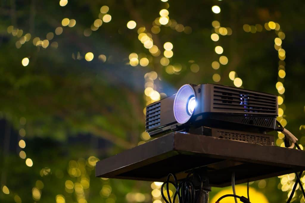A loud projector sits on a specially built projector stand.